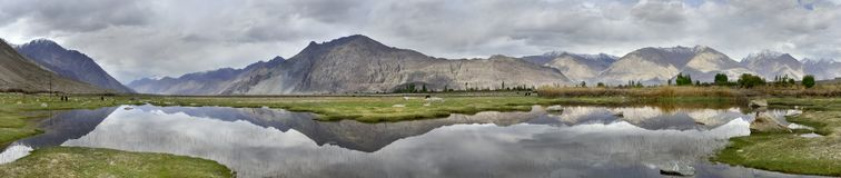 Free Mountain Lake, Soft Grassy Beaches, Flat Water Surface Mirror Peaks And A Gray Cloudy Sky, The Valley Of Nubra, Northern India. Royalty Free Stock Images - 105928029