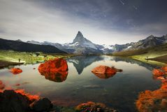 Mountain lake Stellisee   and Shooting Stars. Autumn larches on the background of the Matterhorn and autumn in the Alps. The clear water of the mountain lake royalty free stock photos