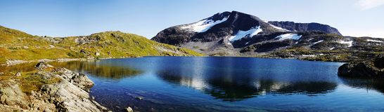 Mountain lake. Still lake in Norway and high mountains in background Stock Photos