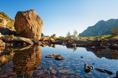 Mountain lake with stone boulder and reflections Stock Photo
