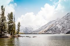 Mountain lake with stones and trees on the shore. Travelling in the mountains Stock Photos