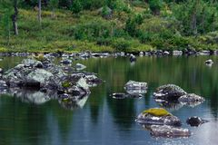 Mountain lake with stones and trees on the shore. Travelling in the mountains Royalty Free Stock Photos
