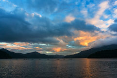 Mountain lake on sunrise with fishing boats in the distance stock images