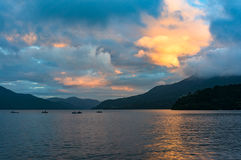Mountain lake on sunrise with fishing boats in the distance stock photo