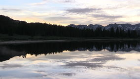 Mountain Lake Sunset Reflection. A scenic sunset reflected in a Colorado mountain lake stock video footage