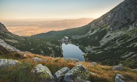 Mountain Lake at Sunset with Rocks in Foreground Royalty Free Stock Photography