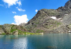 Mountain lake surrounded by beautiful high rocky peaks on a sunny day with blue sky Royalty Free Stock Images