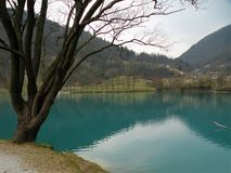 Mountain lake with turquoise blue water, surrounded by alps and green hills. Full peace. Water reflects the city on the coast.Gian stock photos