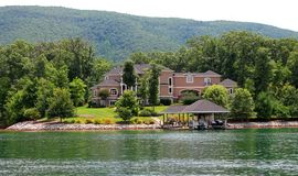 Mountain Lakeside Vacation Home. Large sprawling lakeside vacation villa house with boat dock at shore of Smith Mountain Lake Royalty Free Stock Photography