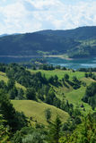 Mountain landscape. With green fields and lake behind Royalty Free Stock Image