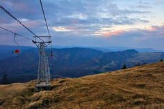 Mountain landscape. Shot of a mountain landscape panorama after the sunset with a chairlift pole in it royalty free stock photography