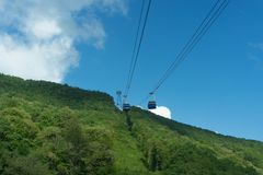 Mountain landscape on background of blue cloudy sky. And a view of the cable car Stock Photos