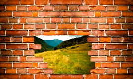 Mountain landscape behind a wall of red bricks. Toned Royalty Free Stock Images