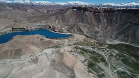 Mountain landscape with blue lake, desert, snow capped mountains and roads. Band-e Amir Lakes. Band-e Amir National Park, Bamyan Province, Afghanistan. Aerial stock video