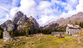 Mountain landscape with blue sky with clouds and ruins of an old farm and a hiker.  stock images