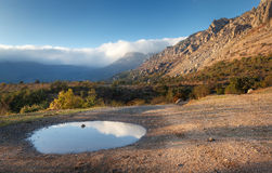 Mountain landscape with blue sky reflection in puddle at sunset Royalty Free Stock Photography