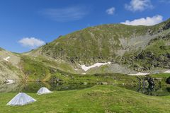 Mountain landscape with camping tents near the lake. Stock Photos
