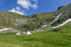 Mountain landscape with camping tents under the summit Royalty Free Stock Photos