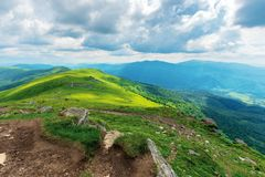 Mountain landscape on cloudy summer noon. Footpath through green alpine meadows. beautiful nature scenery in dappled light. forested distant slopes with rocks royalty free stock image
