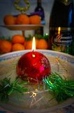 Christmas candle with tangerines. Christmas candle on the table with champagne, tangerines, chocolate Stock Photos