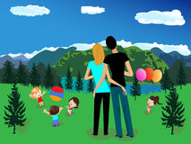 Mountain landscape. With a couple and children playing on the green grass Royalty Free Stock Image