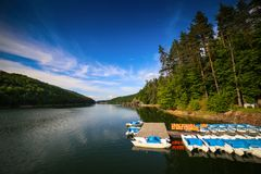 Mountain landscape with docks and pedal cycle boats on lake Gozna surrounded by forest at Valiug. Caras-Severin County, Romania Stock Images