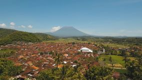 Mountain landscape farmlands and village Bali, Indonesia. Aerial view town near volcano Agung, rice terrace, farmlands, village, fields with crops, agricultural stock video footage