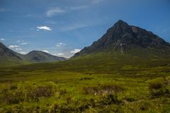 Mountain landscape in the Glencoe area in Scotland, Springtime view mountains with grassland and countryside road in the valley of. The Scottish highland near Stock Images