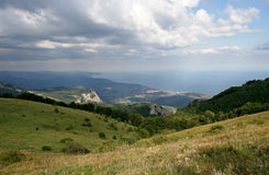 The mountain landscape with green hillsides, distant mountains, far Black sea and sunbeams. Royalty Free Stock Image