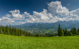 Mountain landscape with green meadow and town in the valley. Stock Photo