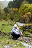Mountain landscape. Happy girl. Beautiful dog. Green trees. Autumn forest Royalty Free Stock Photo