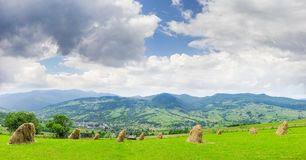 Mountain landscape with hayfield on the foreground. Mountain landscape with hayfield and hay, which is dried on the foreground, mountain village in the valley on Royalty Free Stock Photo