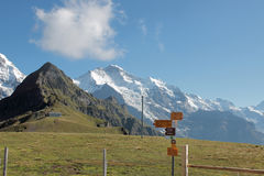 Mountain landscape with hiking route trails signs at high peak Switzerland with signpost Royalty Free Stock Photography
