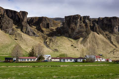 Mountain landscape Iceland. Amazing mountainous landscape of Iceland with houses in foreground Royalty Free Stock Photos