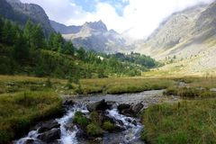 Mountain valley landscape with quiet river. Just a peaceful view of Alps, with a little river coming  down the mountains Stock Photo
