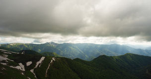 Mountain landscape. Light rays pierces way through the gloomy lo Royalty Free Stock Photography