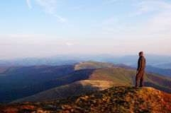 Man standing on top of a mountain royalty free stock photo