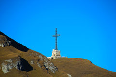 Mountain landscape with metallic cross and a blue sky Stock Photos