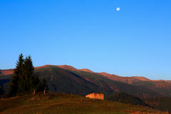 Mountain landscape with the moon and barn early morning. Carpathians mountains, Ukraine, Europe Stock Photos