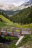 Mountain landscape in north Italy. With a small stream under the wooden bridge and the mountains in the background during the summertime royalty free stock image