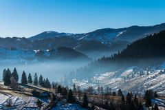 Mountain landscape in northern Romania in winter. Carpathian Mountains, Eastern Europe. Rural scene Royalty Free Stock Photo