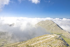 Mountain landscape over the couds. Stock Photos