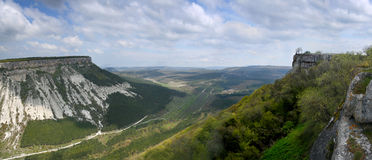 Mountain landscape. Panoramic photo. Panoramic photo of a mountain landscape. A mountain valley of a photo from top. The sky is covered with fast clouds. In the stock photos