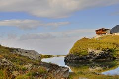 Mountain landscape with pond and chalet Stock Photography