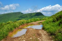 Mountain landscape and puddle on road Stock Photos