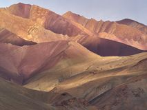 Mountain landscape in red tones: huge red, pink and yellow hills alternate with each other in the rays of setting sun under a gent Royalty Free Stock Photography