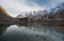 Mountain landscape with reflection on the water. Stone hut stand alone at Karakoram range in Pakistan. Mountain landscaped with reflection on the water. Stone stock photos