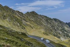 Mountain landscape with road and moving caravan travel trailers. Transfagarasan mountain road panorama . Royalty Free Stock Photo