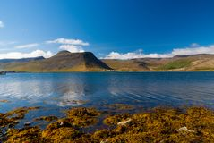 Mountain landscape seen from sea in isafjordur, iceland. Hilly coastline on sunny blue sky. Summer vacation on. Scandinavian island. Discover wild nature Royalty Free Stock Image