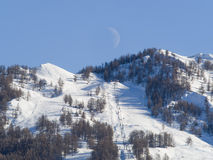 Mountain landscape with ski slopes, ski lifts and half moon Royalty Free Stock Photography